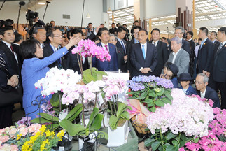Japanese Prime Minister Shinzo Abe (centre, red tie) and Chinese Premier Li Keqiang (blue tie) at garden centre in Eco-rin. Woman on the left: Hokkaido Governor Harumi Takahashi. Photo: Aleph Inc.